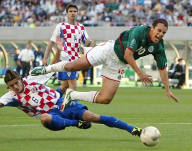 CROATIA'S ZIVKOVIC BRINGS DOWN MEXICO'S BLANCO DURING THEIR WORLD CUP FINALS MATCH IN NIIGATA
